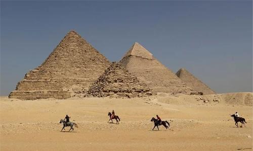 Egypt says probes images of naked couple atop pyramid
